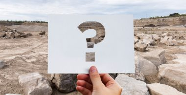 Image of hand holding up a piece of paper with a question mark on it in front of a quarry backdrop.
